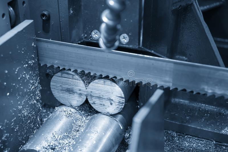 The operation of band saw machine cutting the metal rod. The ingot material preparation for machining process by automatic band saw machine stock photo