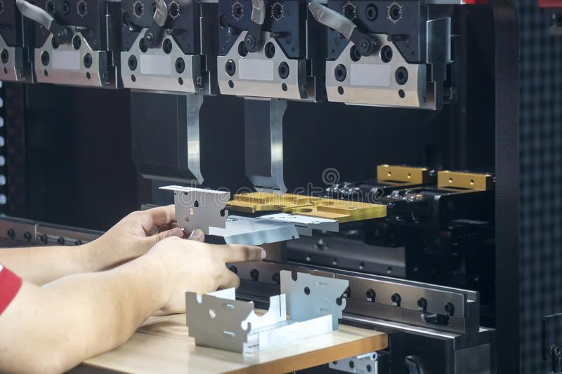 Operation of hydraulic bending machine with forming die by skill operator. Operation of hydraulic bending machine with forming die by skill operator, The sheet royalty free stock image