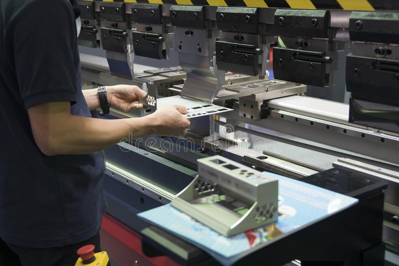 Operation of hydraulic bending machine with forming die by skill operator. The sheet metal manufacturing process by bending machine with technician operator royalty free stock photos
