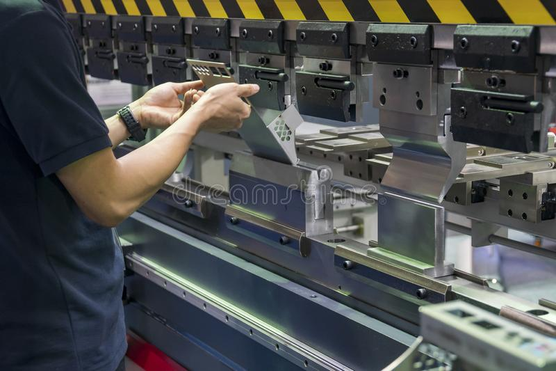 Operation of hydraulic bending machine with forming die by skill operator, The sheet metal manufacturing process . Operation of hydraulic bending machine with royalty free stock image