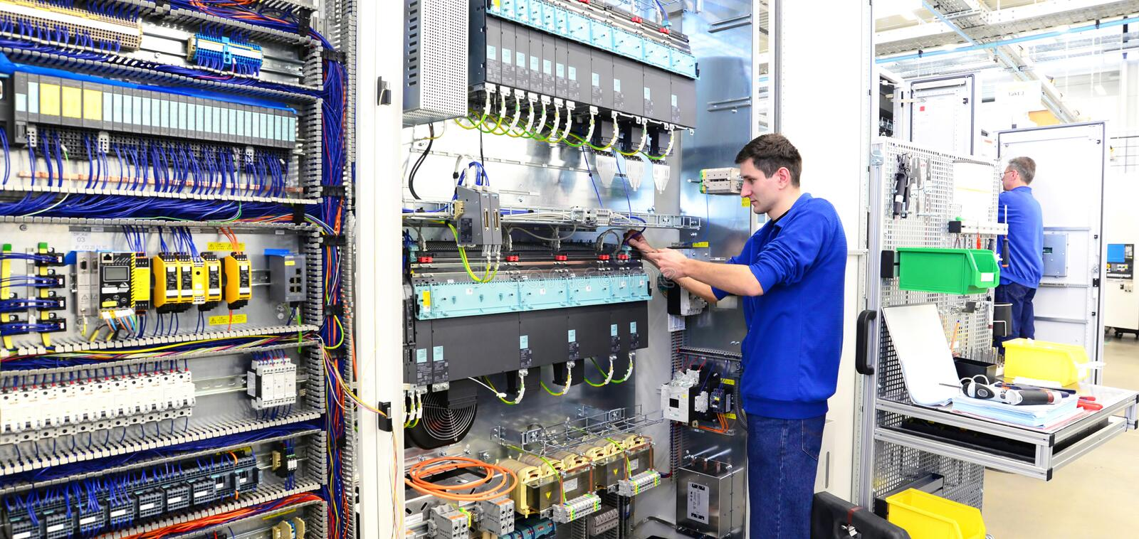 Operator assembles machine in a factory - production of switch c. Abinets for industrial plant - panorama photo stock image