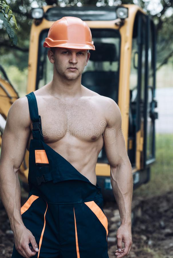 Operator concept. Excavator operator on construction site. Muscular operator in working uniform. Machine operator with stock images