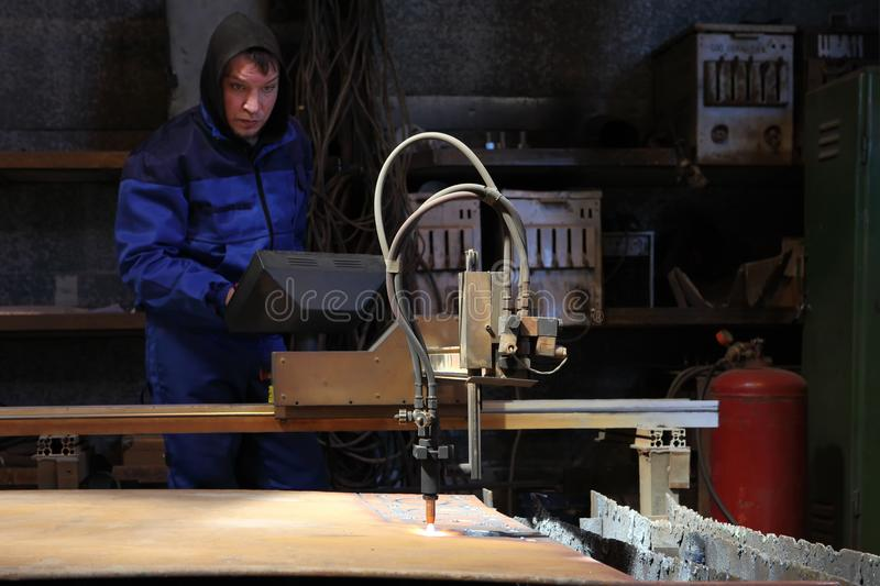 Operator during control CNC plasma machine for metal cutting. St. Petersburg, Russia - May 30, 2017: The worker cuts the steel plate using PC-based CNC machines royalty free stock image
