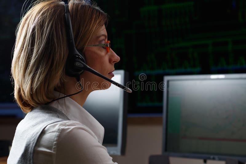 Operator with headphone in power distribution control center. Dispatcher with headphone in power distribution control center stock photography