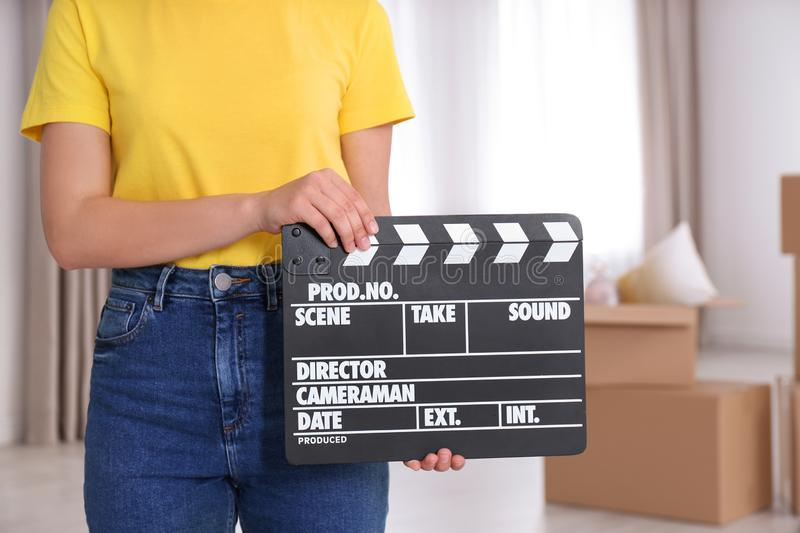 Operator holding clapperboard during the production indoors. Closeup stock images