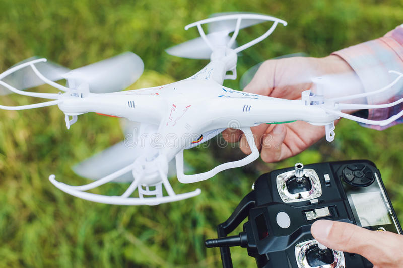 Operator holding remote control and drone. Unmanned aerial copter for photo and video starting in forest. Aeromodelling, hobby, leisure concept royalty free stock images