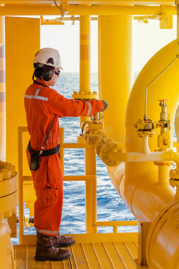 Operator open or close manual operation valve. Of oil and gas process at oil and rig plant, offshore oil and gas industry, offshore oil and rig in the sea royalty free stock image