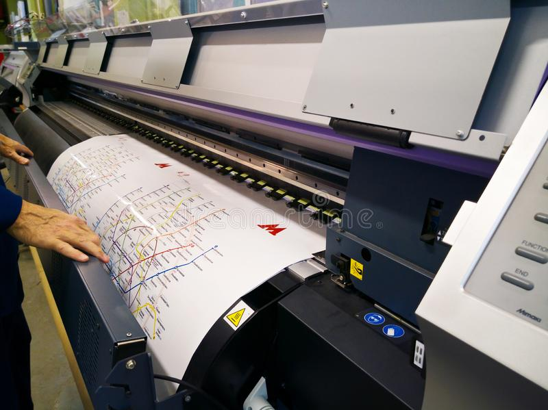 Operator of the professional wide format printer prints map of Moscow metro stock photography