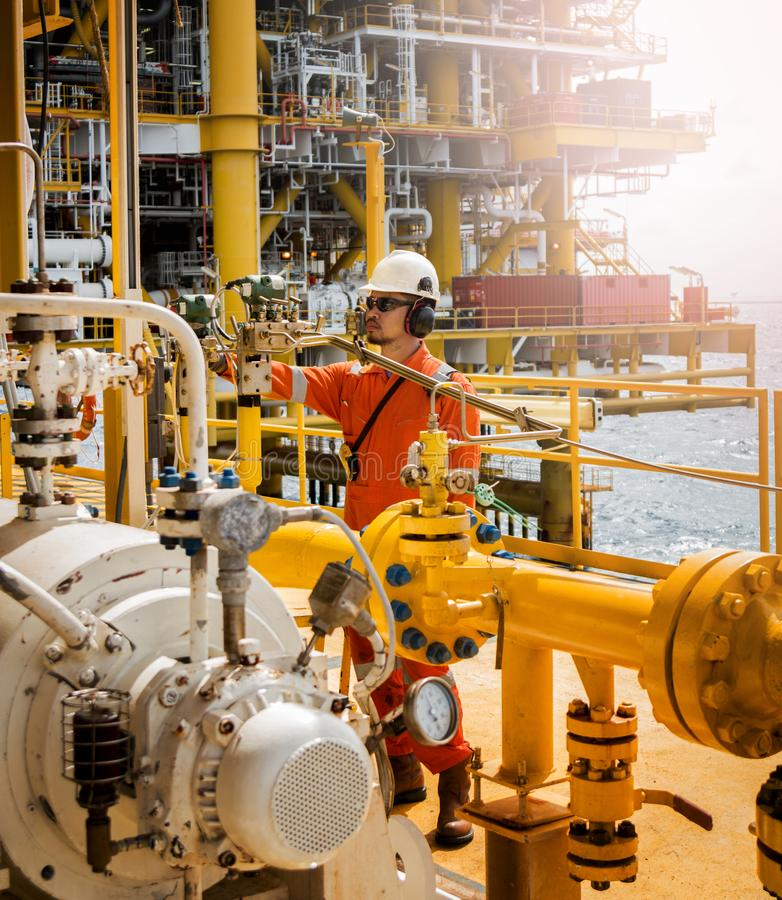 Operator recording operation of oil and gas process at oil and r. Ig plant, offshore oil and gas industry, offshore oil and rig in the sea, operator monitor stock image
