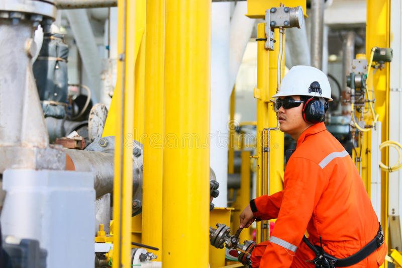Operator recording operation of oil and gas process at oil and rig plant, offshore oil and gas industry, offshore oil and rig. In the sea, operator monitor stock photo