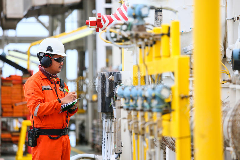Operator recording operation of oil and gas process at oil and rig plant, offshore oil and gas industry, offshore oil and rig. In the sea, operator monitor royalty free stock photography