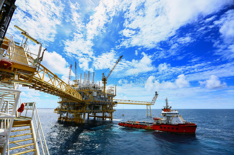 Operator recording operation of oil and gas process at oil and rig plant, offshore oil and gas industry, offshore oil and rig. In the sea, operator monitor royalty free stock photo