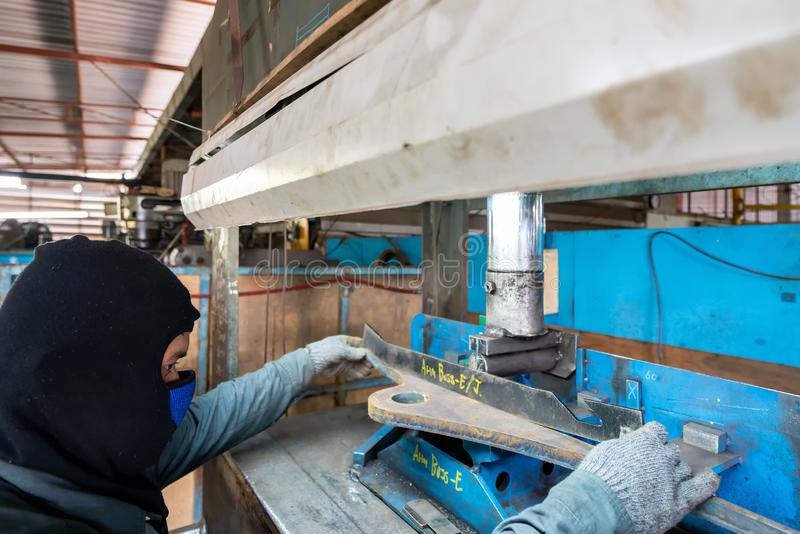 Operator or worker use steel plate for inspection product after press down by manual hydraulic bending machine at factory stock photo