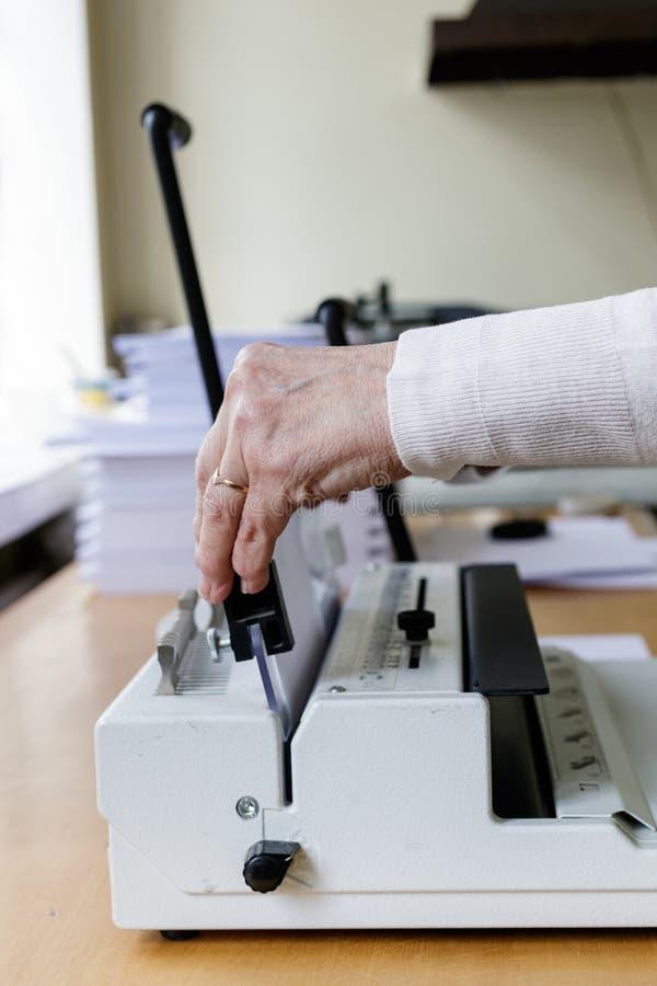 Operatore della rilegatura del libro Lavoro con la macchina di rilegatura del libro immagine stock