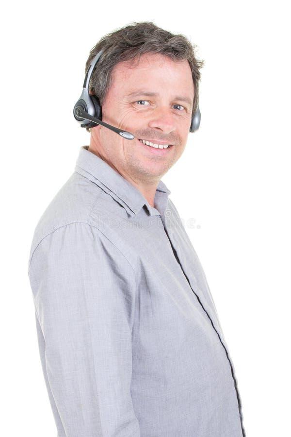 Operatore di call center bello dell'uomo isolato indossando una cuffia avricolare su fondo bianco fotografia stock
