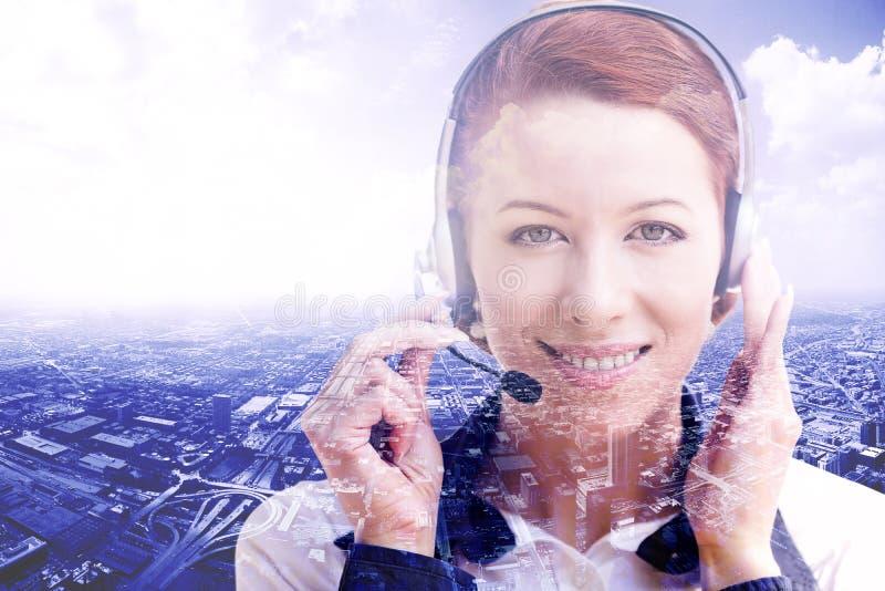 Operatore femminile sorridente del servizio clienti con la cuffia avricolare sul fondo di paesaggio urbano fotografie stock libere da diritti