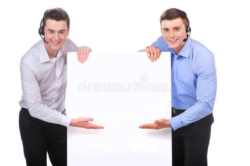Operatore maschio sorridente di servizio di assistenza al cliente che indica il tabellone per le affissioni bianco in bianco fotografia stock libera da diritti