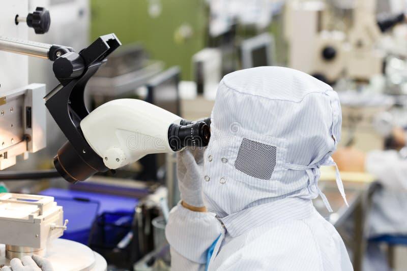 Operatore in microscopio di uso della fabbrica immagini stock