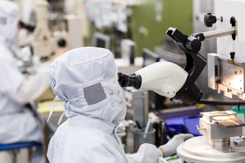 Operatore in microscopio di uso della fabbrica fotografie stock
