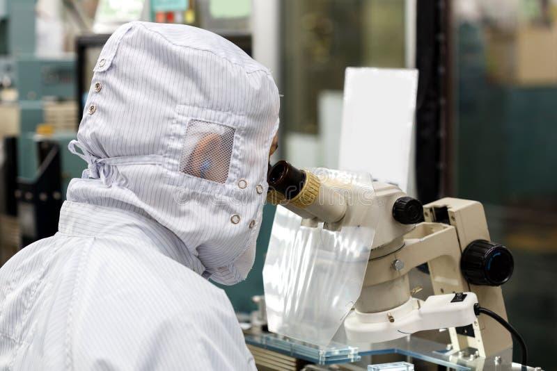 Operatore in microscopio di uso della fabbrica immagine stock