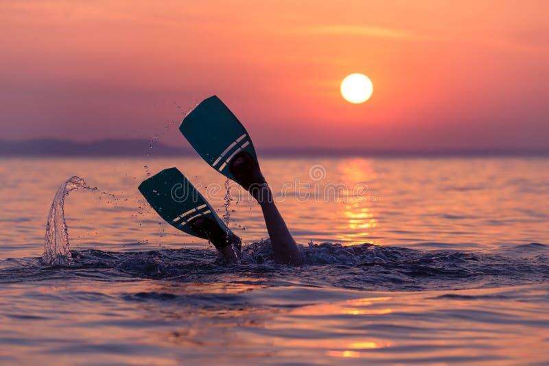 Operatore subacqueo con le alette al tramonto sopra il mare fotografia stock