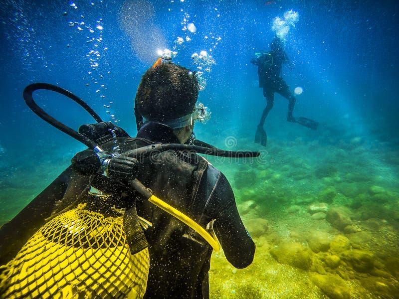 Operatore subacqueo di nuovo alla macchina fotografica, guardante ad un altro operatore subacqueo nel mare fotografia stock