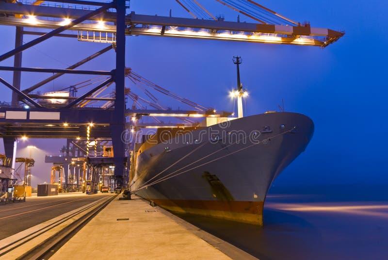 Operazione del contenitore in porto con le gru ed il caricamento del cavalletto/i contenitori di scarico fotografia stock libera da diritti