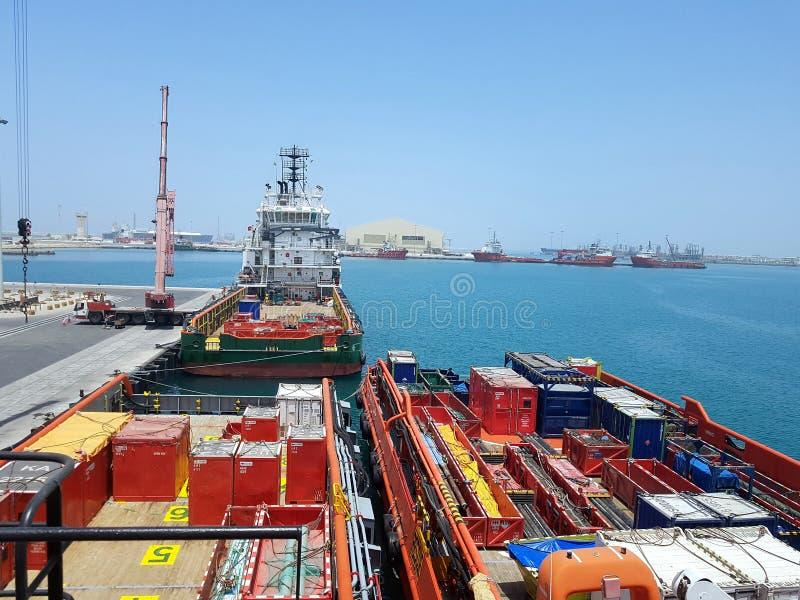 Operazioni del carico in corso a bordo di funzionamento della nave appoggio per le piattaforme offshore Fondo di logistica in oli immagini stock libere da diritti