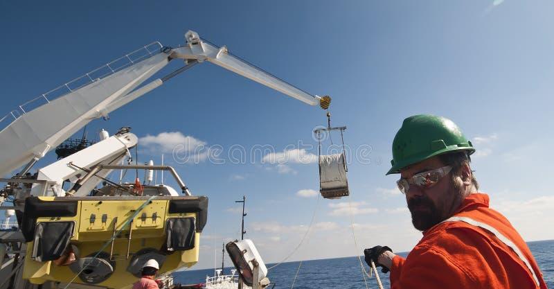 Operazioni di sollevamento della gru offshore - uomini che assistono alle linee di etichetta fotografie stock libere da diritti