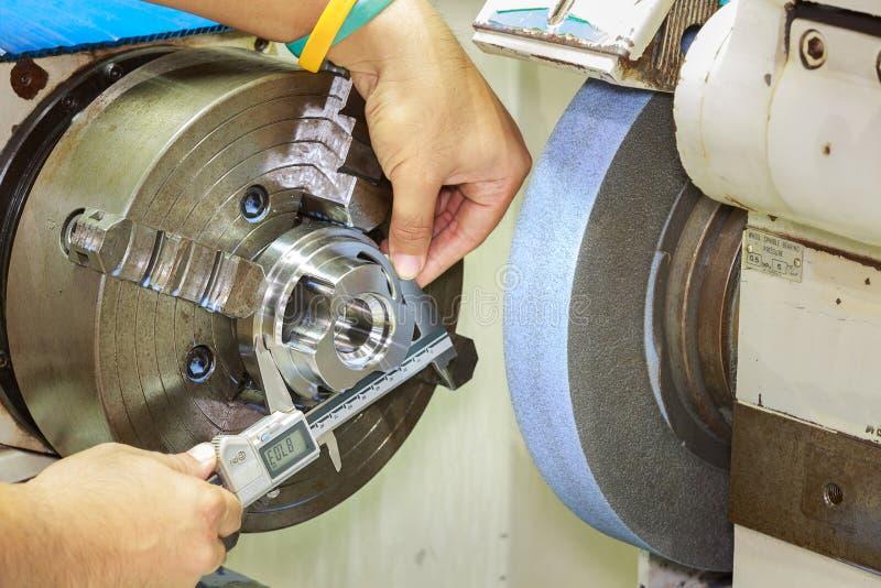 Opertor che misura la parte stridente di CNC fotografie stock