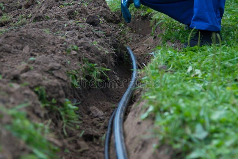 Opgegraven aardegeul voor aanleggen van pijpleidingen van mededeling en elektro bedrading onder de grond om water aan woon te ver stock afbeelding