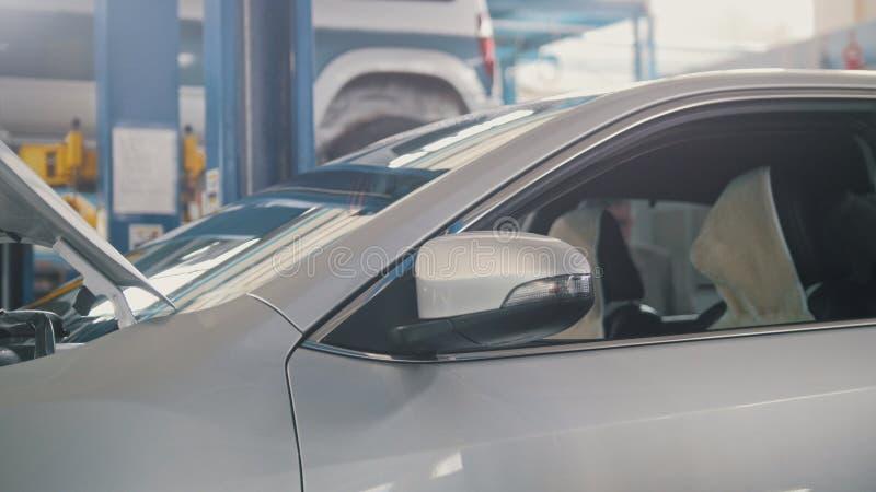 Opgeheven auto in autoworkshop - kleine onderneming stock foto's