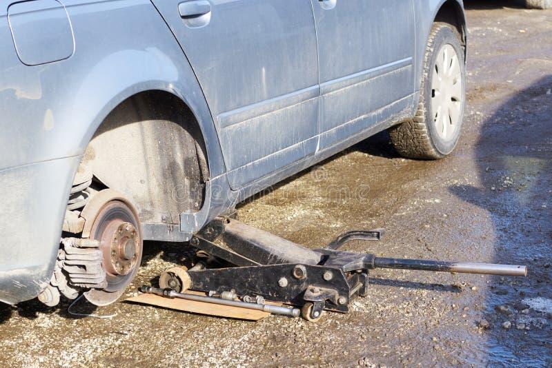 Opgeheven auto en voorbereiding voor het verwijderen van een oude beschadigde remstootkussens en rotor aan vervanging op nieuw royalty-vrije stock afbeelding