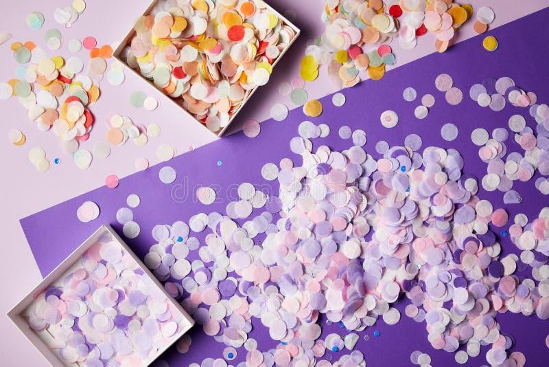 opgeheven mening van confettienstukken in document vakjes en violette oppervlakte royalty-vrije stock fotografie