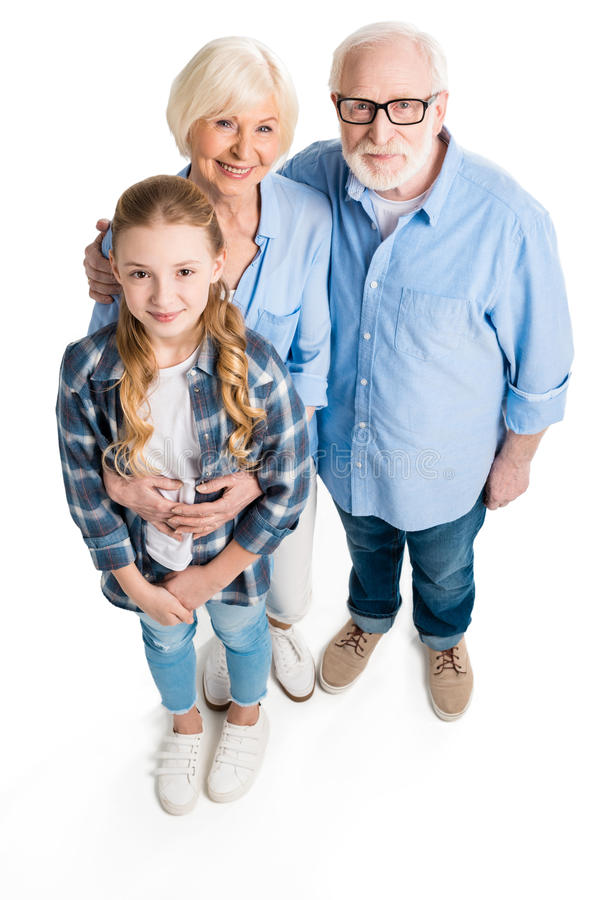 Opgeheven mening van gelukkig grootvader, grootmoeder en kleinkind die en camera koesteren bekijken stock fotografie