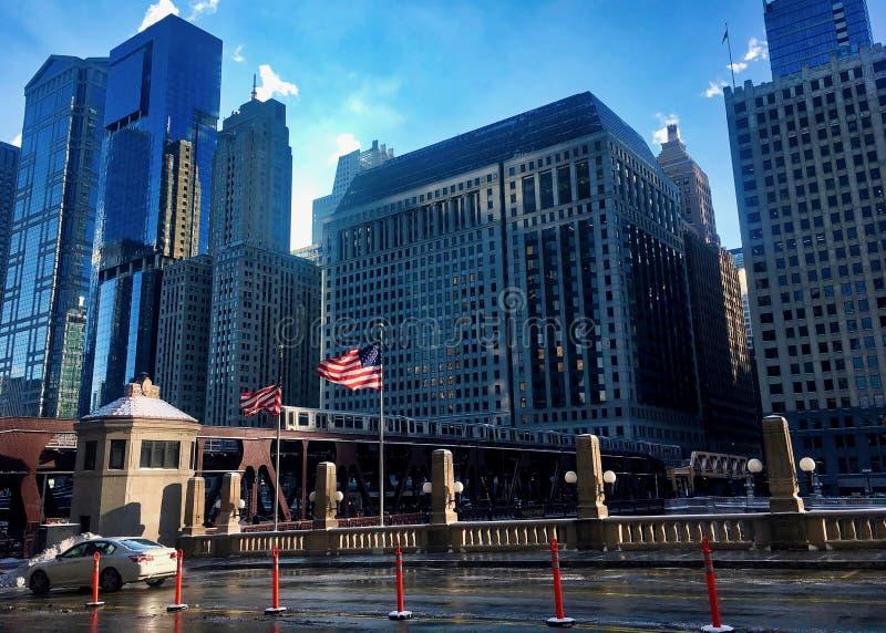 Opgeheven treinpassen over de Rivier van Chicago als Amerikaanse vlaggenvlieg in wind stock afbeeldingen
