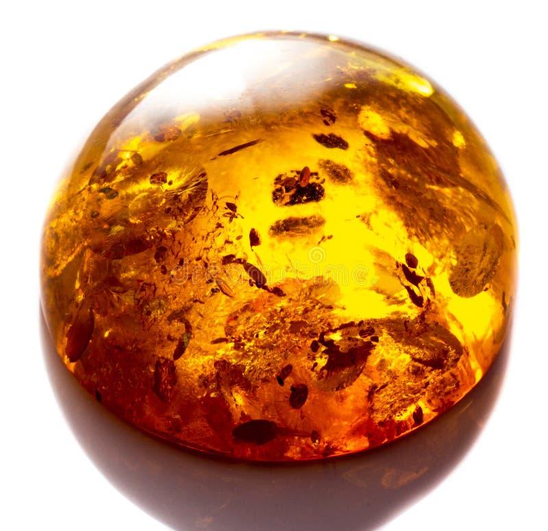 Opgepoetst cabochon van kunstmatige amber met opneming op witte geïsoleerde achtergrond royalty-vrije stock afbeelding