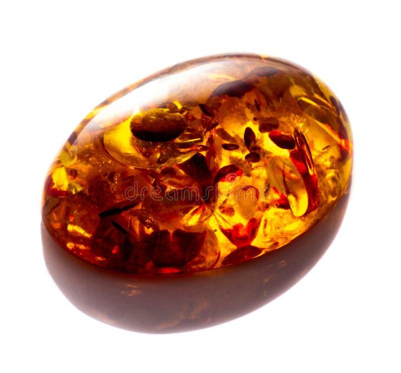 Opgepoetst cabochon van kunstmatige amber met opneming op witte geïsoleerde achtergrond stock fotografie