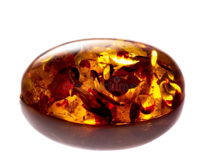 Opgepoetst cabochon van kunstmatige amber met opneming op witte geïsoleerde achtergrond royalty-vrije stock fotografie