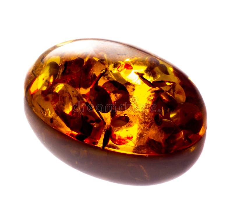 Opgepoetst cabochon van kunstmatige amber met opneming op witte geïsoleerde achtergrond royalty-vrije stock foto