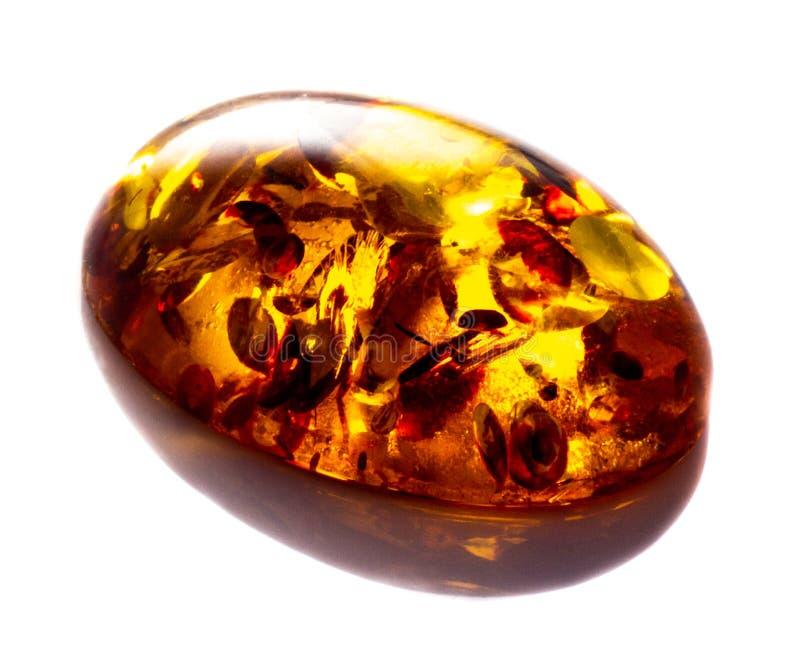 Opgepoetst cabochon van kunstmatige amber met opneming op witte geïsoleerde achtergrond stock afbeelding