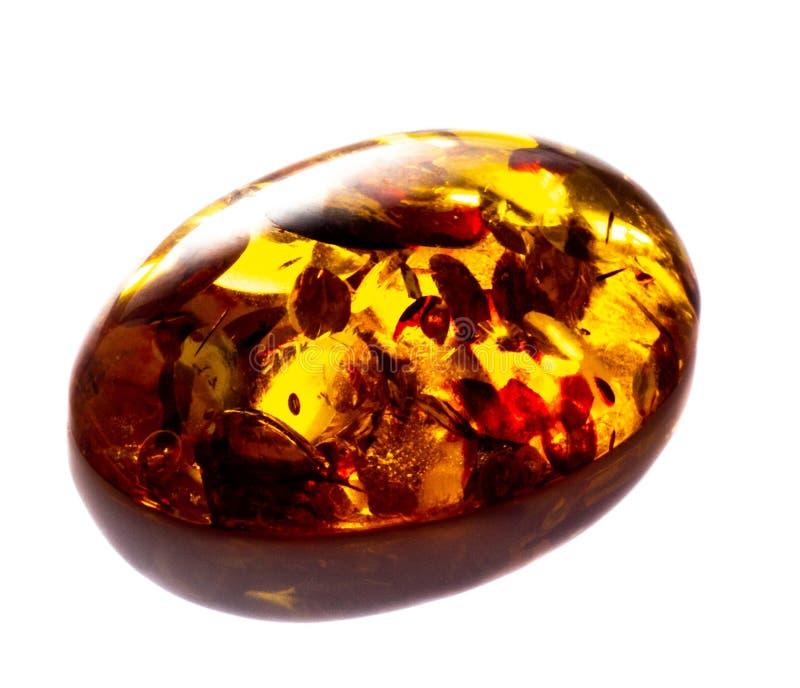 Opgepoetst cabochon van kunstmatige amber met opneming op witte geïsoleerde achtergrond stock afbeeldingen