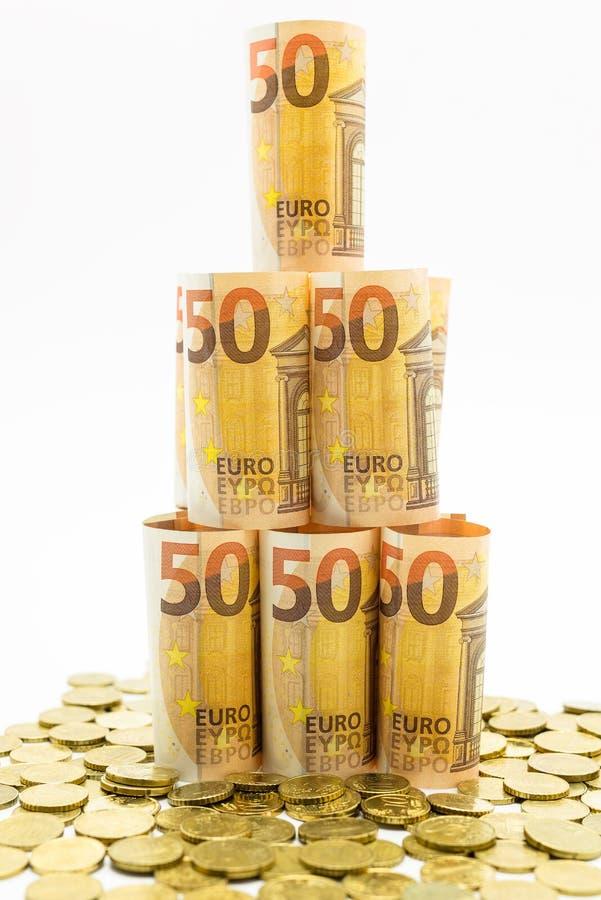 Opgerold 50 euro bankbiljetten in de vorm van een piramide met euro muntstukken Geïsoleerd op een witte achtergrond royalty-vrije stock foto