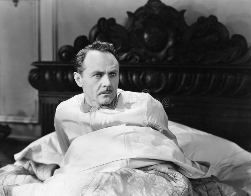 Opgeschrokken mens die omhoog in bed zitten royalty-vrije stock foto's