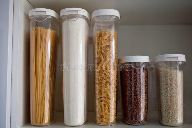 Opgeslagen keukenvoorraadkast met voedsel - deegwaren, boekweit, rijst en suiker De organisatie en de opslag in keuken van een ge royalty-vrije stock foto's