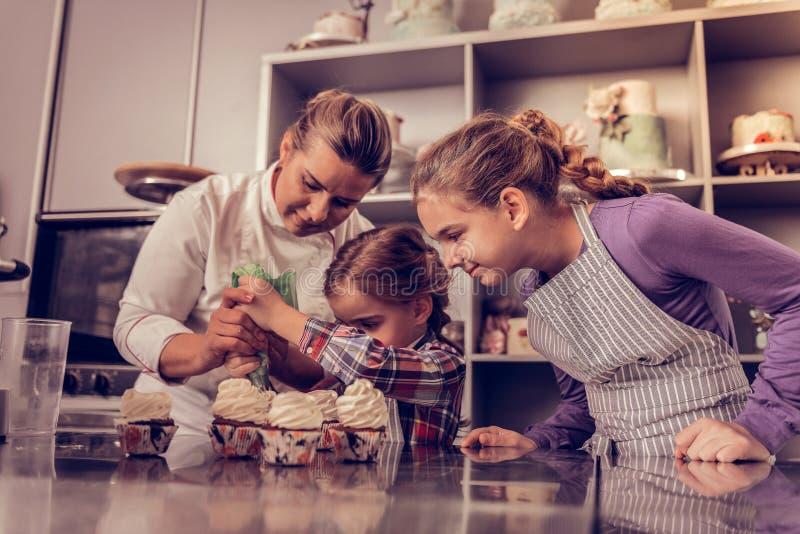 Opgetogen aardige meisjes die room op cupcakes zetten royalty-vrije stock foto's