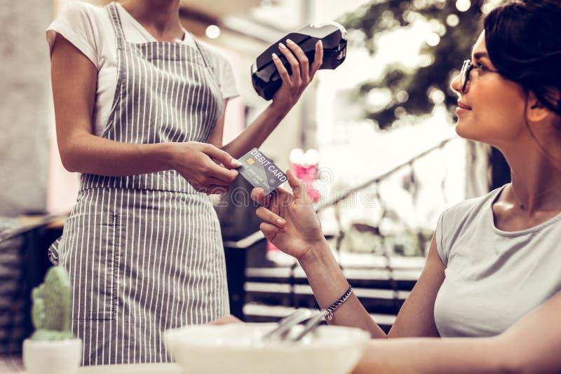 Opgetogen aardige vrouw die haar debetkaart geven stock afbeelding