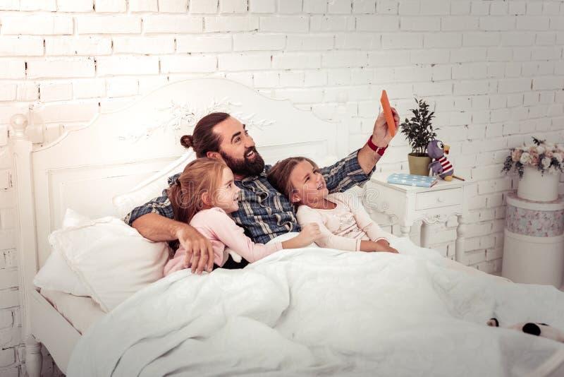 Opgetogen blije mens die selfies met zijn dochters nemen stock afbeelding