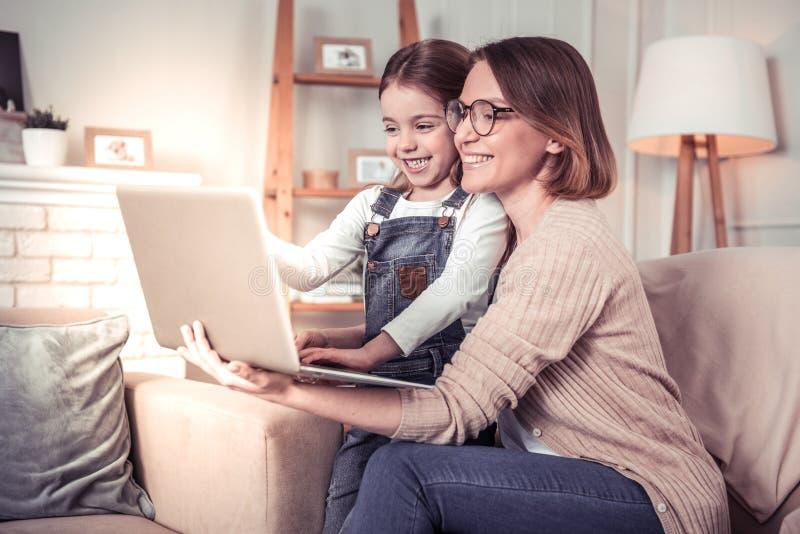 Opgetogen blije moeder en dochter die het laptop scherm bekijken stock fotografie