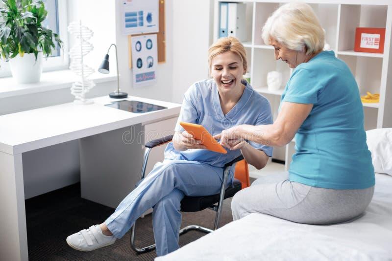 Opgetogen blije vrouw die een beeld tonen aan haar patiënt stock afbeeldingen